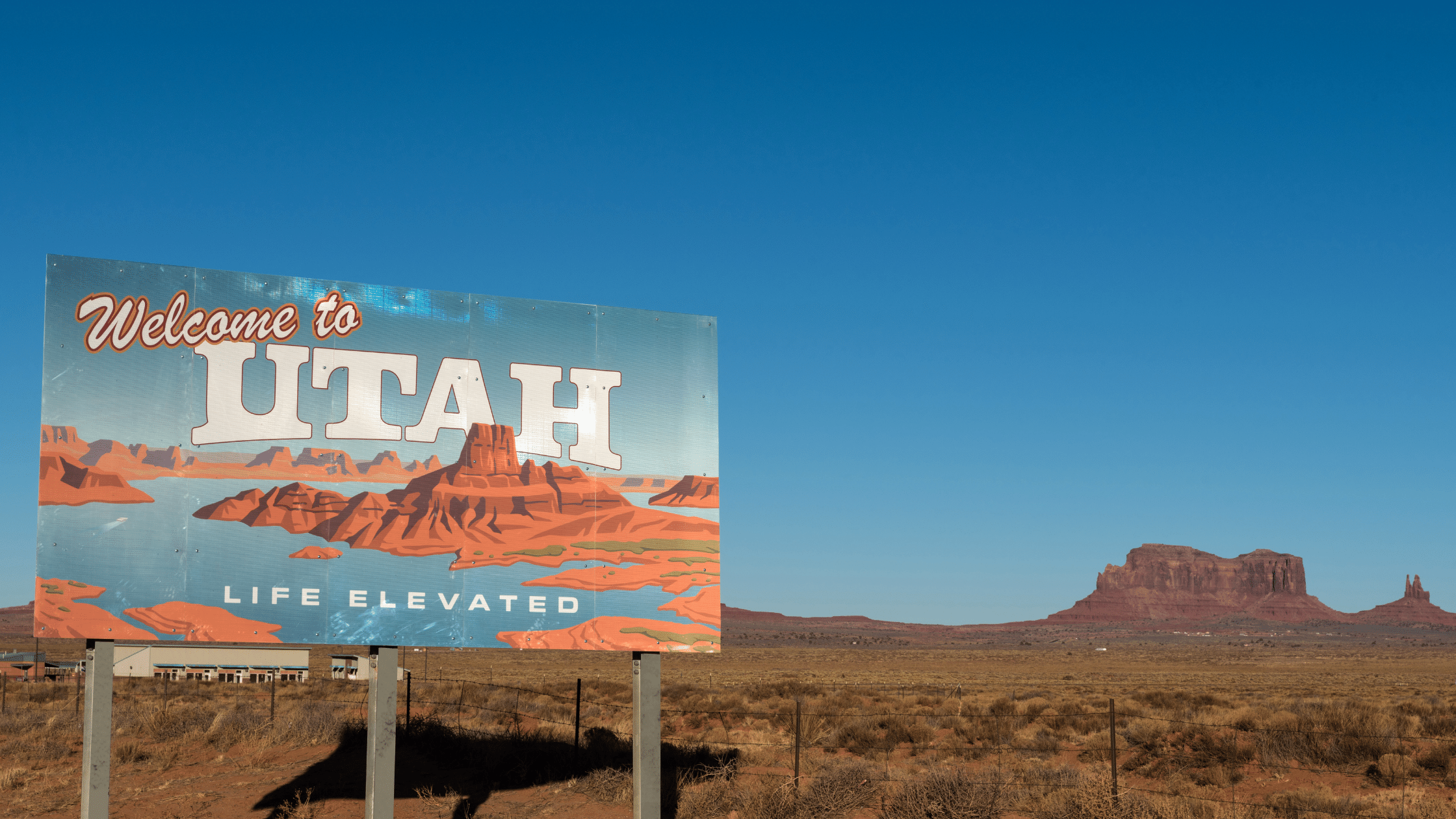 Welcome to Utah sign in the foreground, mountain butte in the background