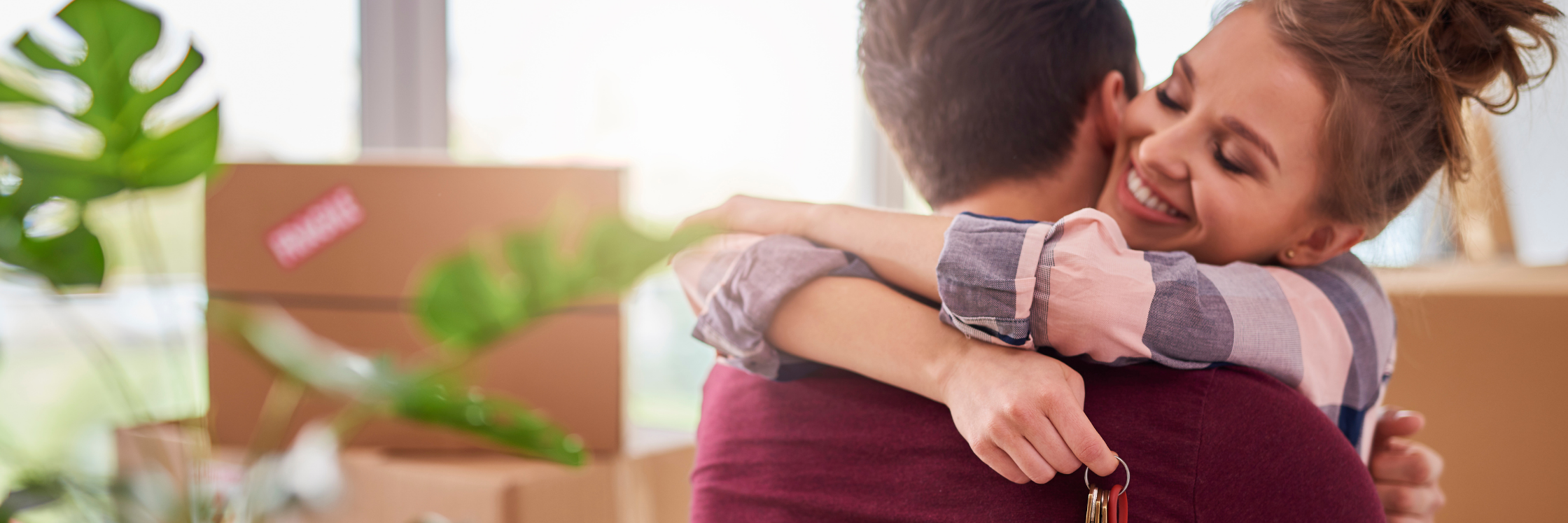couple hugging in front of moving boxes
